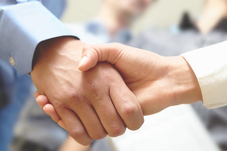 2 Personen geben sich die Hand - eine Nahaufnahme der Hände