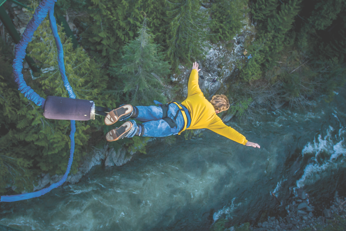 Sprung eines Bungee-Jumpers über einem Fluss
