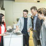Foto von Ausstellern die Besuchern ihr Produkt erklären
