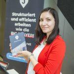 Foto einer Frau, die einen Folder präsentiert