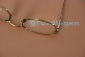 Bild einer Brille mit Text Grundlagen auf einem Blatt darunter