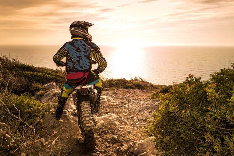 Motocrossfahrer vor Steilküste mit Blick auf das Meer