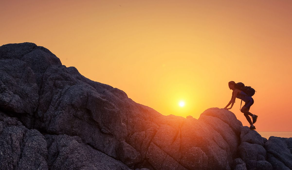 Bild einer Wanderin auf einem Felsmassiv bei Sonnenaufgang