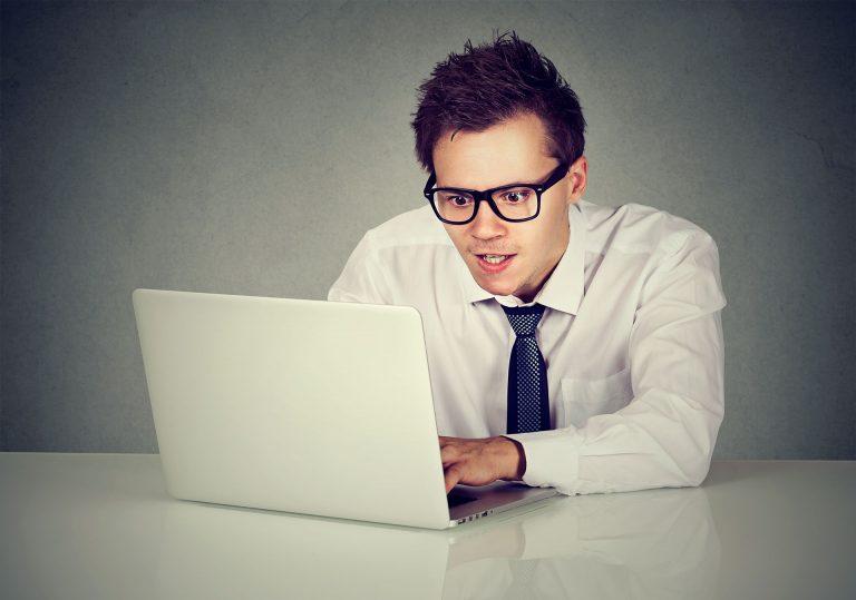 Foto eines jungen Mannes mit Anzug und Brille vor einem Laptop