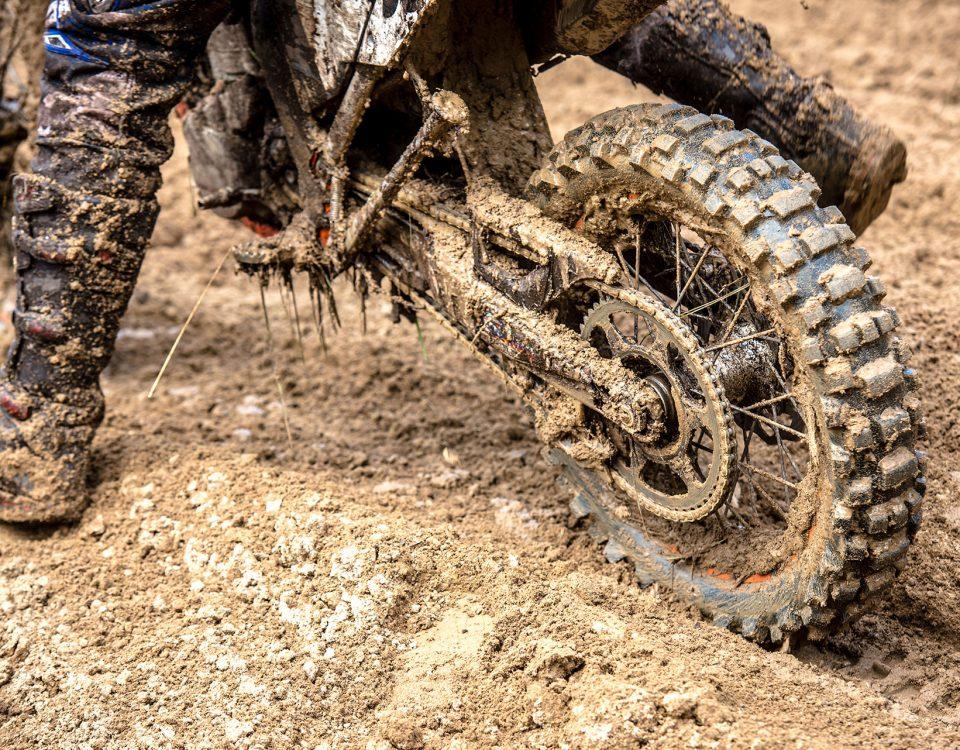 Nahaufnahme eines schlammigen Motorrads und Motorradstiefel