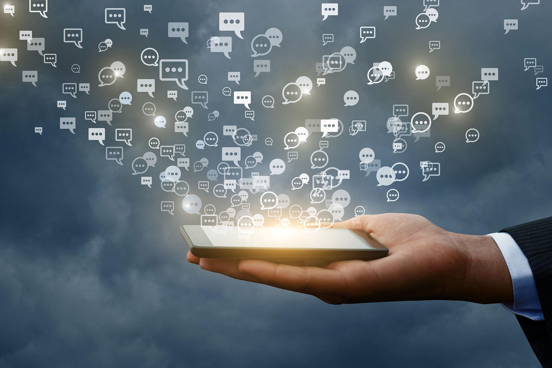 Ein Smartphone liegt auf der Handfläche eines Mannes, Kommentarsymbole steigen vom Smartphone auf