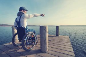 Mann in Rollstuhl steht auf einem Steg und zeigt auf das Meer