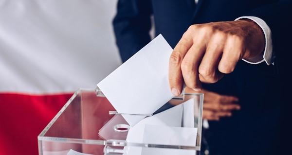 Foto Mann wirft Stimmzettel in Urne