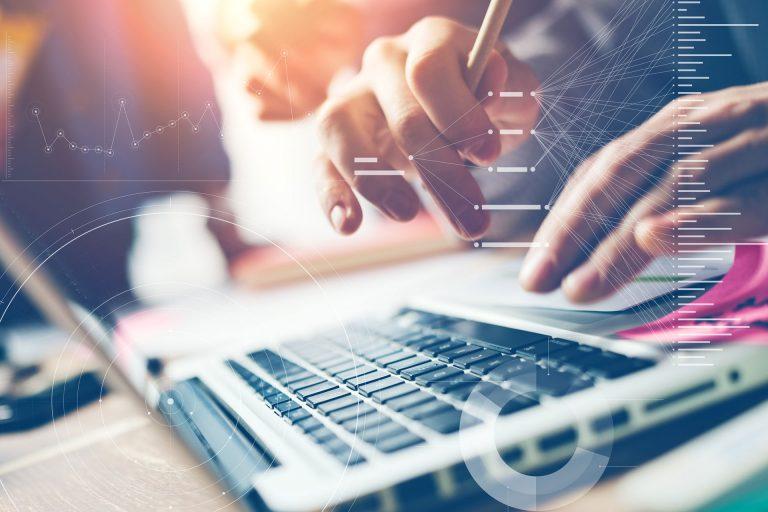 Hände auf einer Tastatur mit grafischer Einblendung von Charts