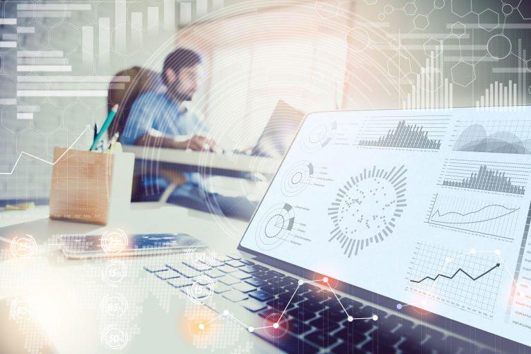 Nahaufnahme von Grafiken am Laptop-Bildschirm und Mann am Schreibtisch im Hintergrund
