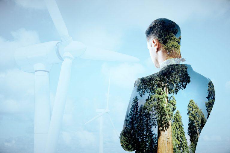 Mann von hinten fotografiert überlappt mit Waldmotiv und Windpark im Hintergrund