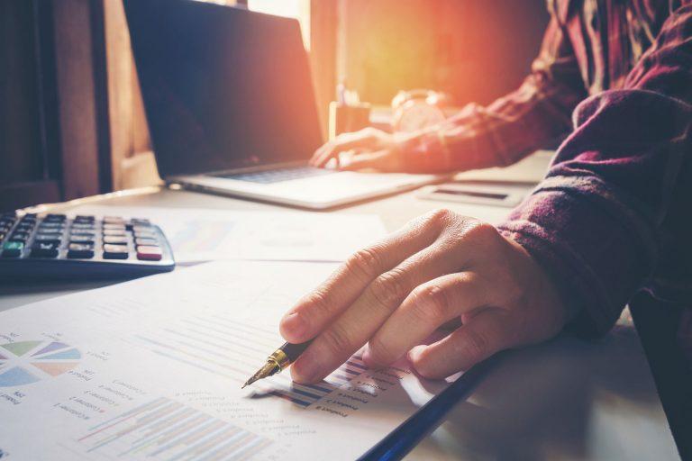 Arme eines Mannes mit Füllfeder in der Hand vor einer gedruckten Tabelle, einem Taschenrechner und einem Laptop
