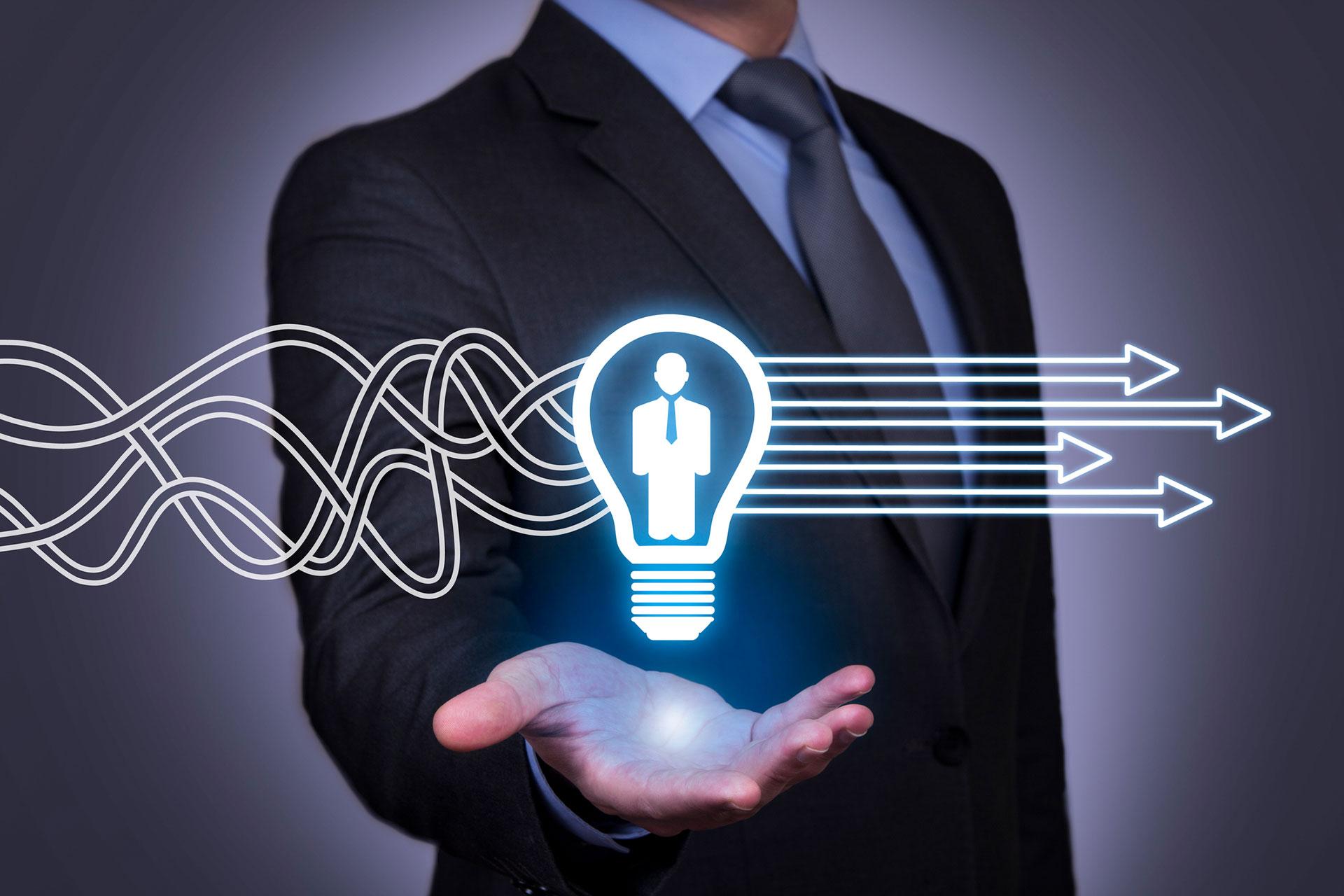 Oberkörper einer Mannes im Anzug der eine digitale Glühbirne in der Hand hält