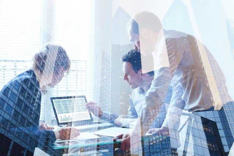 3 Personen vor einem Laptop hinter spiegelnden Wolkenkratzern